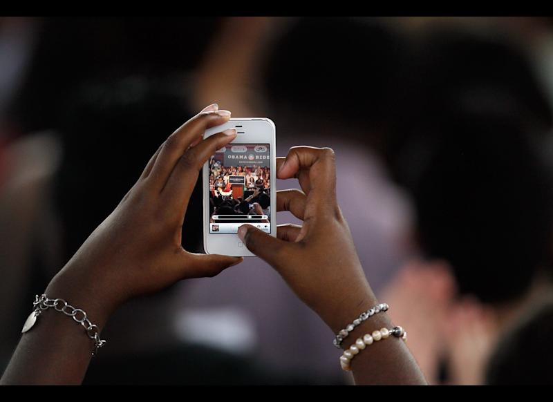 A supporter takes a picture of first lady Michelle Obama as she speaks to supporters and volunteers at the Barbara Goleman High School on July 10, 2012, in Miami Lakes, Florida. Obama spoke about what's she says is at stake in this years presidential election for Floridians.