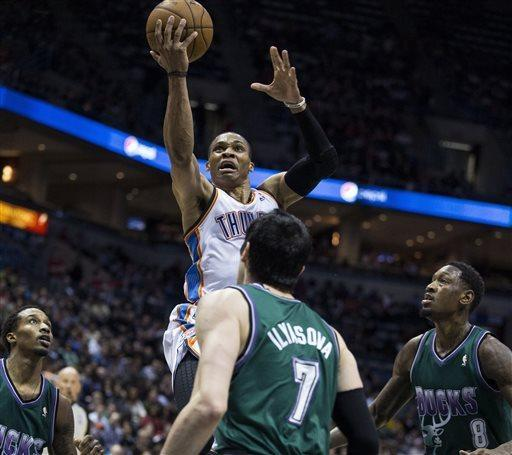 Oklahoma City Thunder's Russell Westbrook, top, shoots over Milwaukee Bucks' Brandon Jennings, left, Ersan Ilyasova, center, and Larry Sanders during the first half of an NBA basketball game on Saturday, March 30, 2013, in Milwaukee. (AP Photo/Tom Lynn)