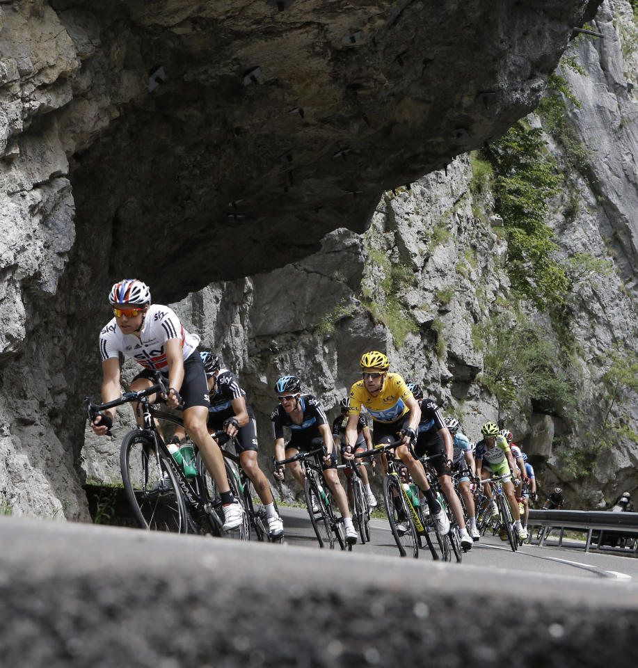 Bradley Wiggins of Britain, wearing the overall leader's yellow jersey, follows teammate Edvald Boasson Hagen of Norway, left, as they speed down Granier pass during the 12th stage of the Tour de France cycling race over 226 kilometers (140.5 miles) with start in Saint-Jean-de-Maurienne and finish in Annonay, France, Friday July 13, 2012. (AP Photo/Laurent Cipriani)