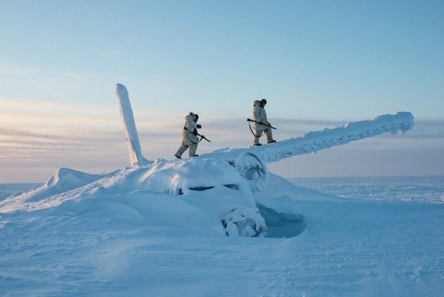 Canadian soldiers climb on the wreckage of a plane, roughly a thousand miles south of the North Pole, to scout the area during an Arctic survival course on Cornwallis Island. As the Arctic warms and tensions over its future rise, the Canadian and US militaries have stepped up operations in the region. (National Geographic/Louie Palu)