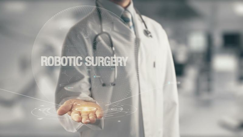 "Physician with stethoscope around neck and palm extended beneath a computer-generated image with the words ""robotic surgery."""