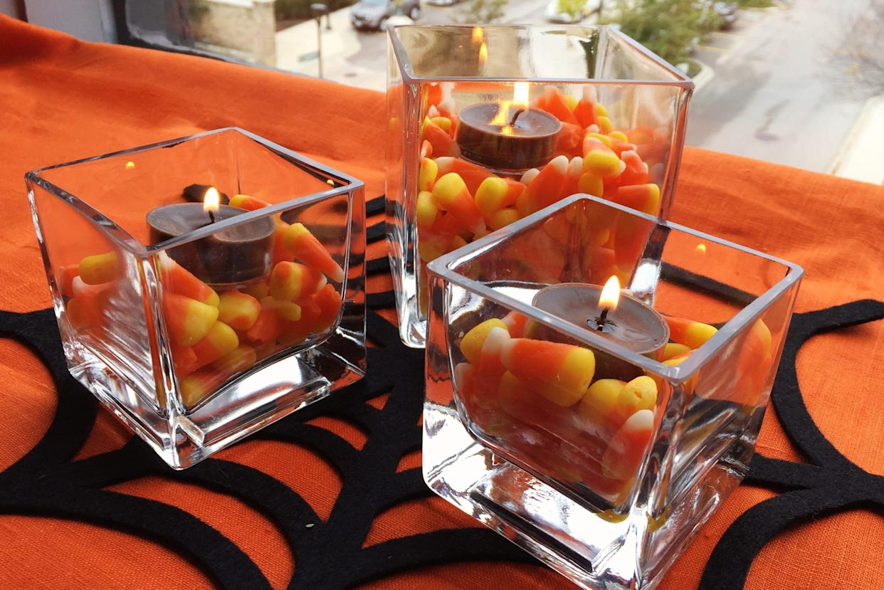 Three candy corn candles constituting a centerpiece