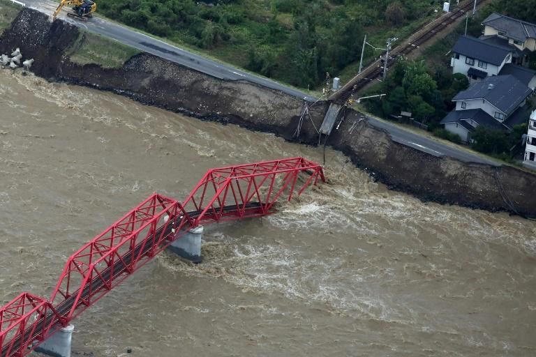 The Chikuma river, heavily swollen by rain from Typhoon Hagibis, swept away part of a train bridge in Ueda, in Japan's Nagano prefecture
