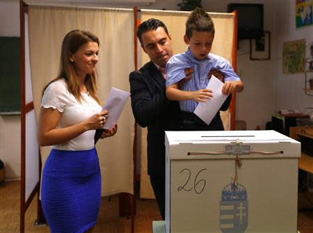 Gabor Vona, the chairman of the far-right Jobbik party, casts his ballot helped by his son Benedek next to his wife Krisztina during European Parliamentary elections in Budapest May 25, 2014. Reuters/Laszlo Balogh