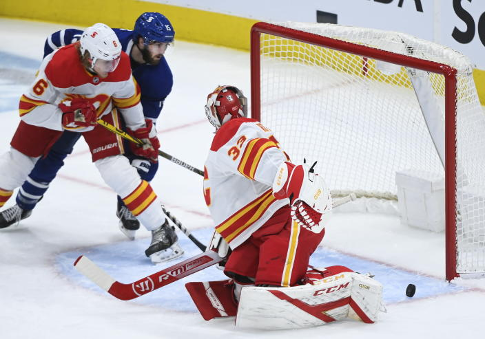 Calgary Flames goaltender David Rittich (33) makes a save but loses sight of the puck as Toronto Maple Leafs center Alexander Kerfoot (15) and Flames defenceman Juuso Valimaki (6) look on during the second period of an NHL hockey game in Toronto on Monday, Feb. 22, 2021. (Nathan Denette/The Canadian Press via AP)