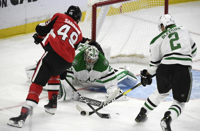 Dallas Stars goaltender Anton Khudobin (35) and defenseman Jamie Oleksiak (2) attempt to get the puck away from Ottawa Senators right wing Scott Sabourin (49) during the first period of an NHL hockey game Sunday, Feb. 16, 2020, in Ottawa, Ontario. (Justin Tang/The Canadian Press via AP)