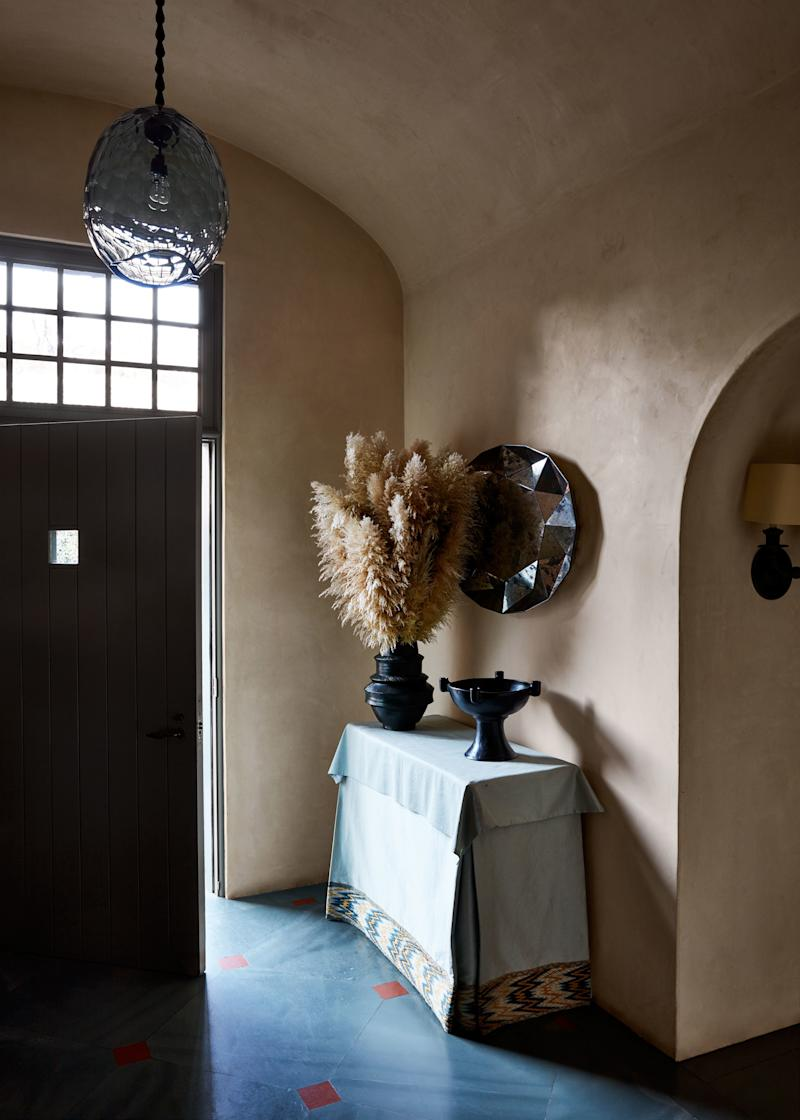 A pendant by David Wiseman hangs in the entry. Oaxacan bowl atop console covered in an 18th-century English flame-stitch fabric; mirror by Sam Orlando Miller.