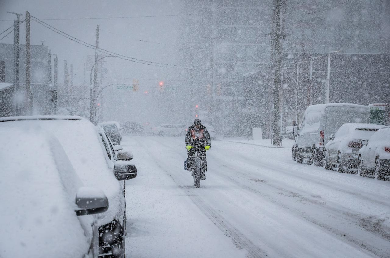 <p>A cyclist makes his way through heavy snowfall in Vancouver, on February 10, 2019. THE CANADIAN PRESS/Darryl Dyck </p>