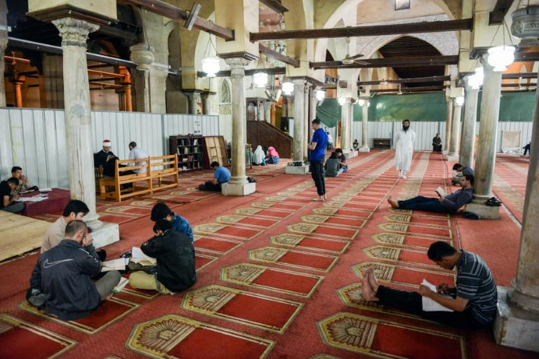 Worshippers sit, pray and read from the Koran inside the 10th century historic al-Azhar mosque in the Egyptian capital Cairo's Islamic quarter