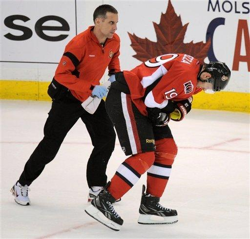 Ottawa Senators' Jason Spezza is helped off the ice by a trainer after receiving a hit to the side of the head by New York Rangers defenseman Marc Staal during the second period of Game 4 of a first-round NHL hockey Stanley Cup playoff series against the Ottawa Senators in Ottawa, Ontario, Wednesday, April 18, 2012. (AP Photo/The Canadian Press, Sean Kilpatrick)