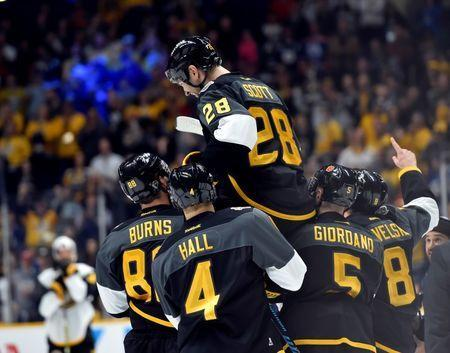Jan 31, 2016; Nashville, TN, USA; Pacific Division forward John Scott (28) of the Montreal Canadiens is picked up by his teammates after beating the Atlantic Division during the championship game of the 2016 NHL All Star Game at Bridgestone Arena. Mandatory Credit: Christopher Hanewinckel-USA TODAY Sports