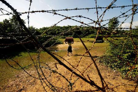 FILE PHOTO: A Rohingya man carrying his belongings approaches the Bangladesh-Myanmar border in Bandarban, an area under Cox's Bazar authority