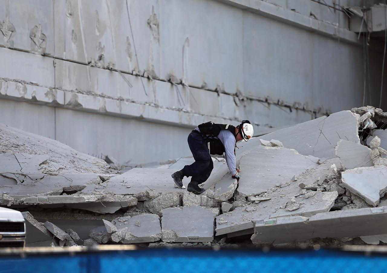 DORAL, FL - OCTOBER 10: A Miami-Dade Fire Rescue search and rescue worker searches in the rubble of a four-story parking garage that was under construction and collapsed at the Miami Dade College's West Campus on October 10, 2012 in Doral, Florida.  Early reports indicate that one person was killed, at least seven people injured and one is still trapped.  (Photo by Joe Raedle/Getty Images)
