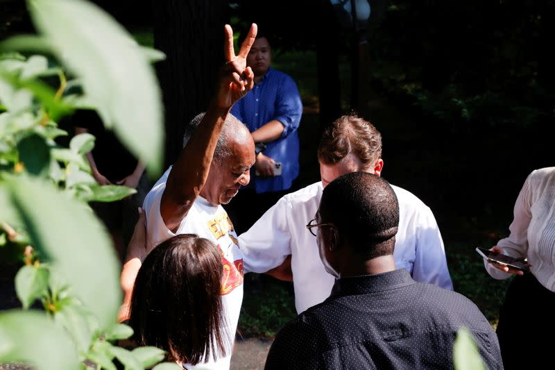 """Bill Cosby flashes a """"V"""" sign outside his house after Pennsylvania's highest court overturned his sexual assault conviction and ordered him released from prison immediately, in Elkins Park"""