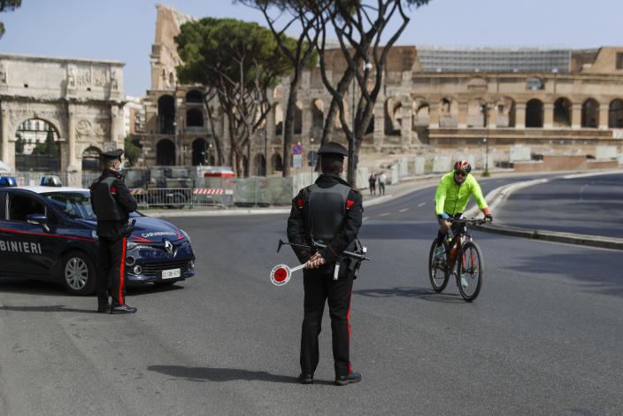 A cyclist rides past Carabinieri police officers at road block near the Colosseum, in downtown Rome, Saturday, April 3, 2021. Italy went into lockdown on Easter weekend in its effort to battle then Covid-19 pandemic. (AP Photo/Gregorio Borgia)