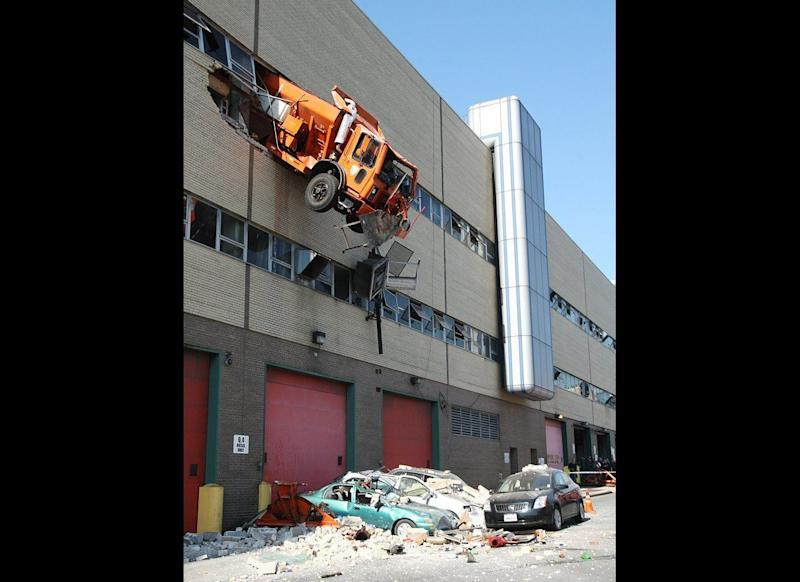 """A 16-ton salt spreader blasted through the fifth-floor wall of a Queens Sanitation Department garage and came within inches of plummeting 50 feet to the street. The driver survived the spectacular 9:30 am crash, which sent bricks and debris raining down on cars parked outside the Maspeth repair facility, but spent 15 terrified minutes dangling in the cab of the bright orange vehicle. It's unclear how driver Robert Legall, a 10-year Sanitation veteran with a clean record, lost control of the big rig. """"There are signs up there warning drivers to slow down,"""" Commissioner John Doherty told the New York Post. """"He's familiar with the rules. We think it was just an unfortunate accident."""""""