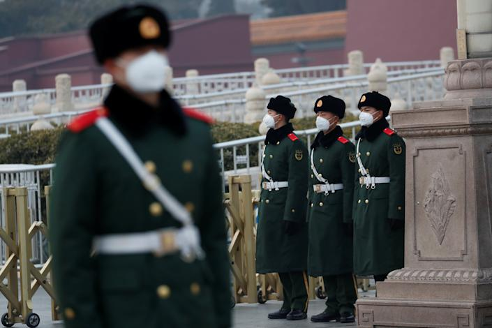 Officers wearing face masks stand guard at the Tiananmen Gate, Beijing, China (Picture: Reuters)