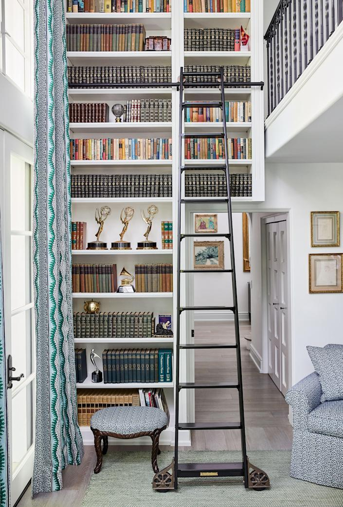 """The room that is now the home office is actually one of the features that originally sold Rivers on the house. She says, """"I hate feeling cramped, and I never respond to houses that are lots of little rooms. And this room had all this light and all this space."""" Bookshelves feature many of her mother's awards, entire encyclopedia sets Rivers had found in storage, and vintage atlases collected by her father, a history buff. As for the matching fabric throughout, Rivers loves that """"sort of English look"""" where the curtains and the chair and everything is the same. The vibe reminds her of the library in her mother's apartment, as well."""