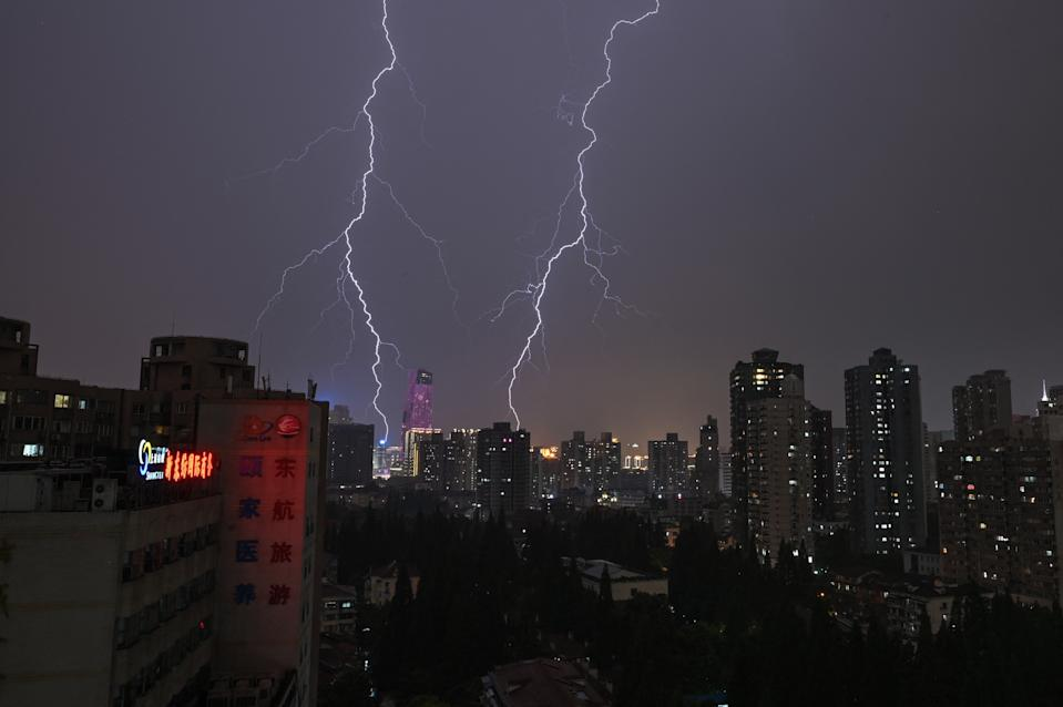 TOPSHOT - Lightning strikes during a thunderstorm over Shanghai on May 14, 2021. (Photo by Hector RETAMAL / AFP) (Photo by HECTOR RETAMAL/AFP via Getty Images)