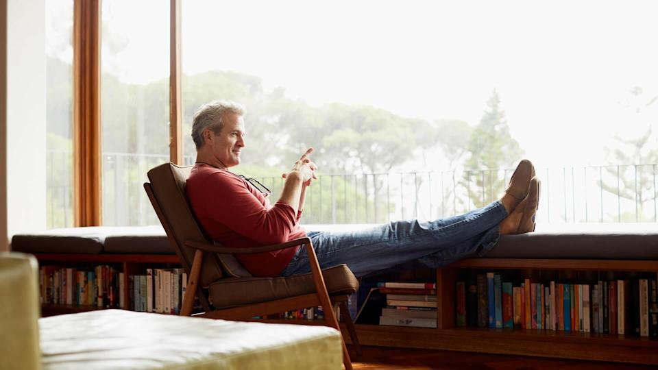 Full length side view of thoughtful mature man relaxing on armchair at home.