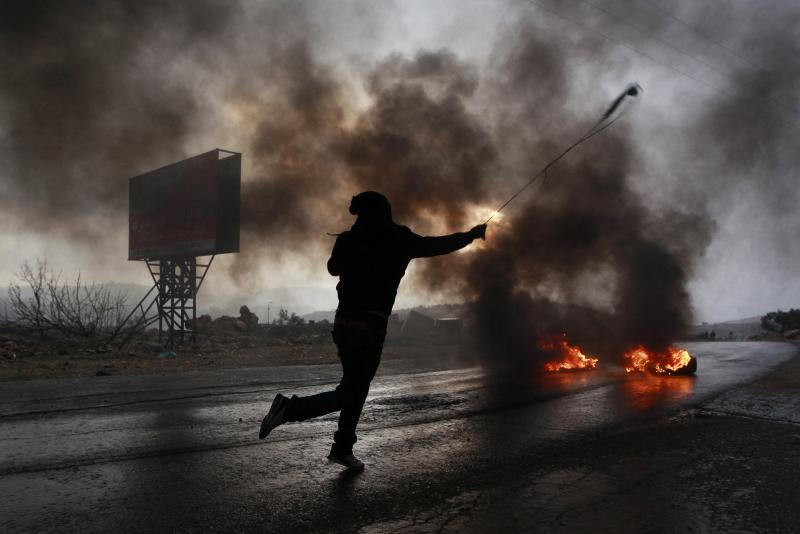 A Palestinian protester uses a sling to hurl a stone during clashes with Israeli troops at a protest near Ramallah