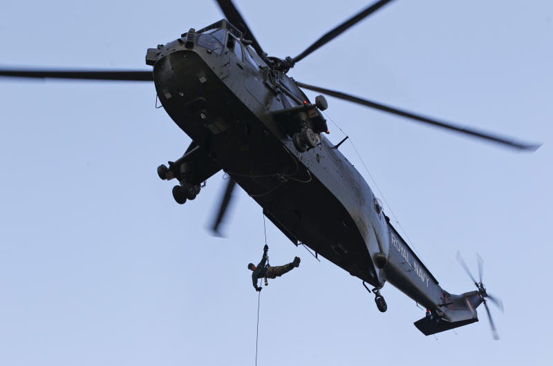 British Royal Marine Martyn Williams, 23, with a lantern with the Olympic flame strapped to his body, abseils from a Sea King helicopter, by the riverside at the Tower of London, Friday, July 20, 2012. Williams was wounded in a road mine attack during a deployment in Afghanistan in 2008 and since fully recovered. The Olympic Torch arrived in London after it was carried around England in a relay of torchbearers to make its way to the London 2012 Olympic Games opening ceremony on July 27, 2012. (AP Photo/Lefteris Pitarakis)