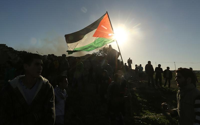 A Palestinian protester holds a flag during clashes with Israeli security forces along the border with Israel in the eastern suburbs of Gaza City on December 4, 2015 (AFP Photo/Mahmud Hams)