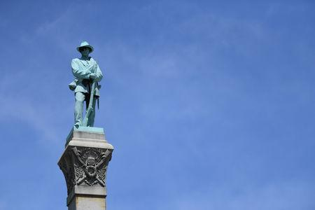 A statue of a Confederate soldier stands high above the crowd during a dedication ceremony in Brandenburg