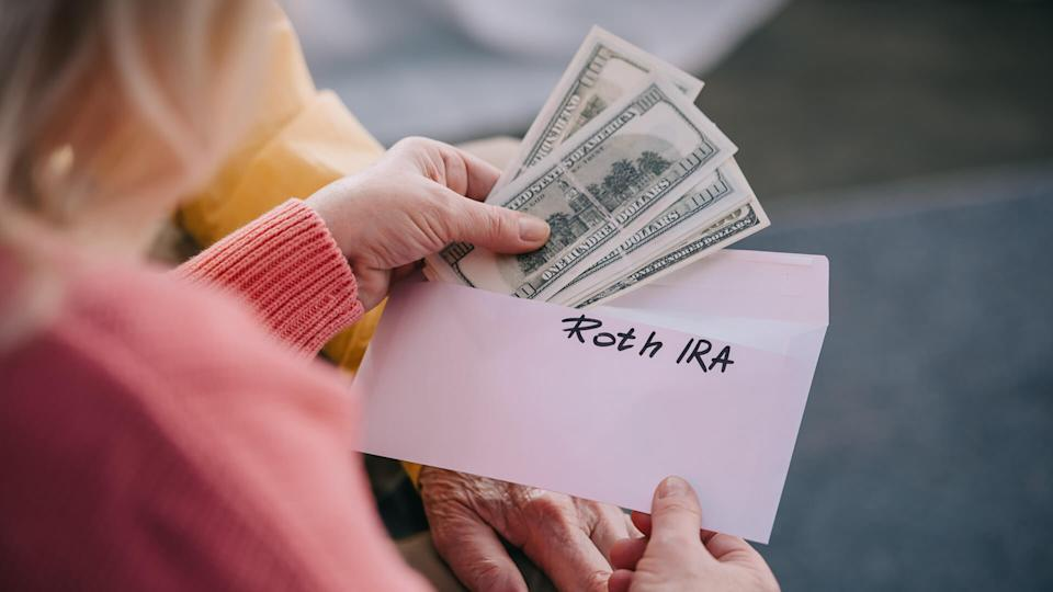 grandparents holding envelope with hundred dollar bills for ROTH