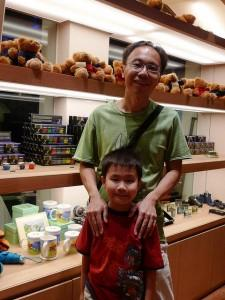 Man in a store, with his son in front of him