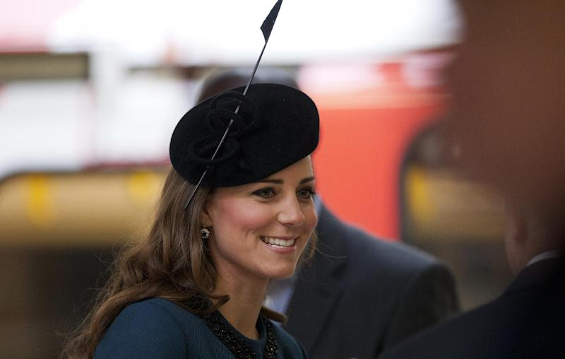 Britain's Kate, the Duchess of Cambridge, speaks to someone at Baker Street underground station in London, for a visit to mark the 150th anniversary of the London Underground, Wednesday, March 20, 2013. Britain's Queen Elizabeth II made her first public engagement in more than a week Wednesday after cancellations following her hospitalization for a stomach bug. The British head of state joined her husband Prince Philip and their granddaughter-in-law, Kate, for the event marking the 150th anniversary of London's sprawling subway system, affectionately known as the Tube. (AP Photo/Matt Dunham)