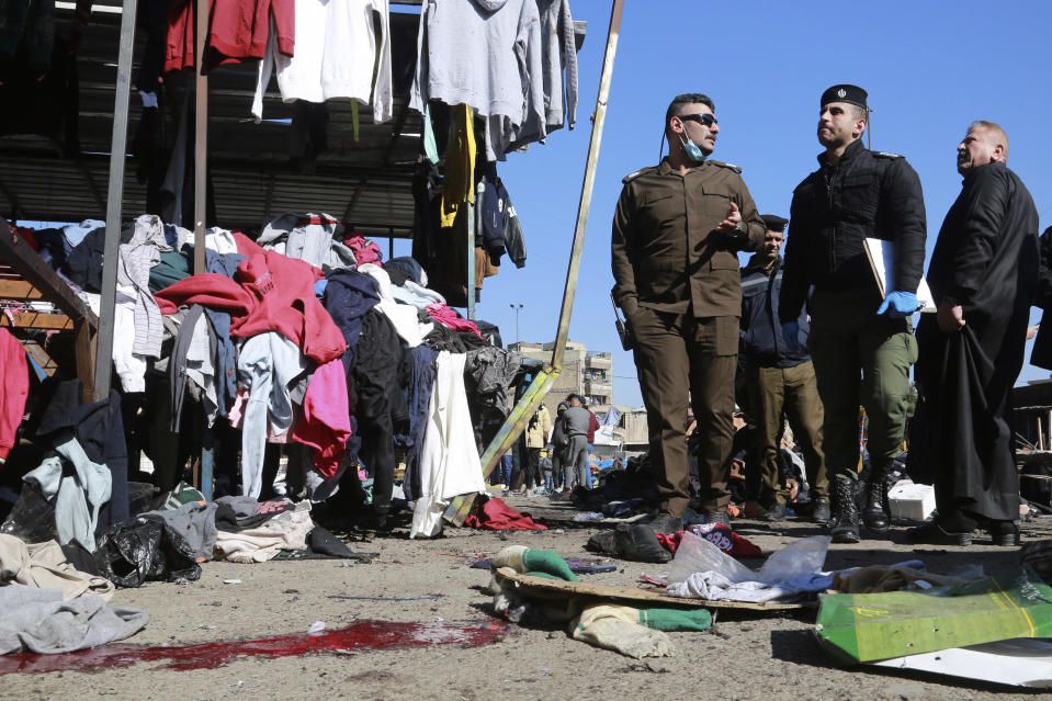 "FILE - In this Thursday, Jan. 21, 2021, file photo, security forces work at the site of a deadly bomb attack in a market selling used clothes, in Baghdad, Iraq. The Islamic State group has claimed responsibility for a rare suicide attack that rocked central Baghdad, killing 32 people and wounding dozens. In a statement late Thursday, the group said the bombing ""targeted apostate Shiites."" (AP Photo/Hadi Mizban, File)"