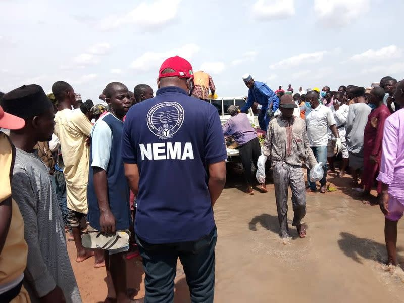 An official of the National Emergency Management Agency stands as people gather around a truck carrying bodies of the victims of a boat accident in Kebbi