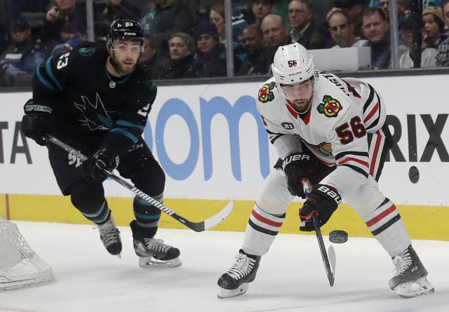 Chicago Blackhawks defenseman Erik Gustafsson (56) watches the puck in front of San Jose Sharks right wing Barclay Goodrow during the first period of an NHL hockey game in San Jose, Calif., Thursday, March 28, 2019. (AP Photo/Jeff Chiu)