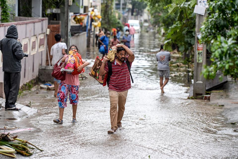 Residents carrying their belongings make their way on a flooded street following heavy rains in Hyderabad on October 14, 2020. (Photo by NOAH SEELAM / AFP) (Photo by NOAH SEELAM/AFP via Getty Images)