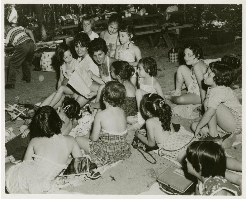 Young woman reading to girls at country camp, circa 1950, from the National Jewish Welfare Board Records.