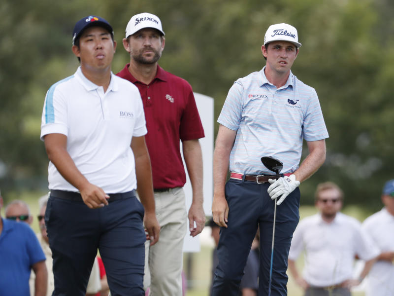 Byeong Hun An, left, and George McNeill, center, watch the drive from the second tee by J.T. Poston during the third round of the Sanderson Farms Championship golf tournament in Jackson, Miss., Saturday, Sept. 21, 2019. (AP Photo/Rogelio V. Solis)