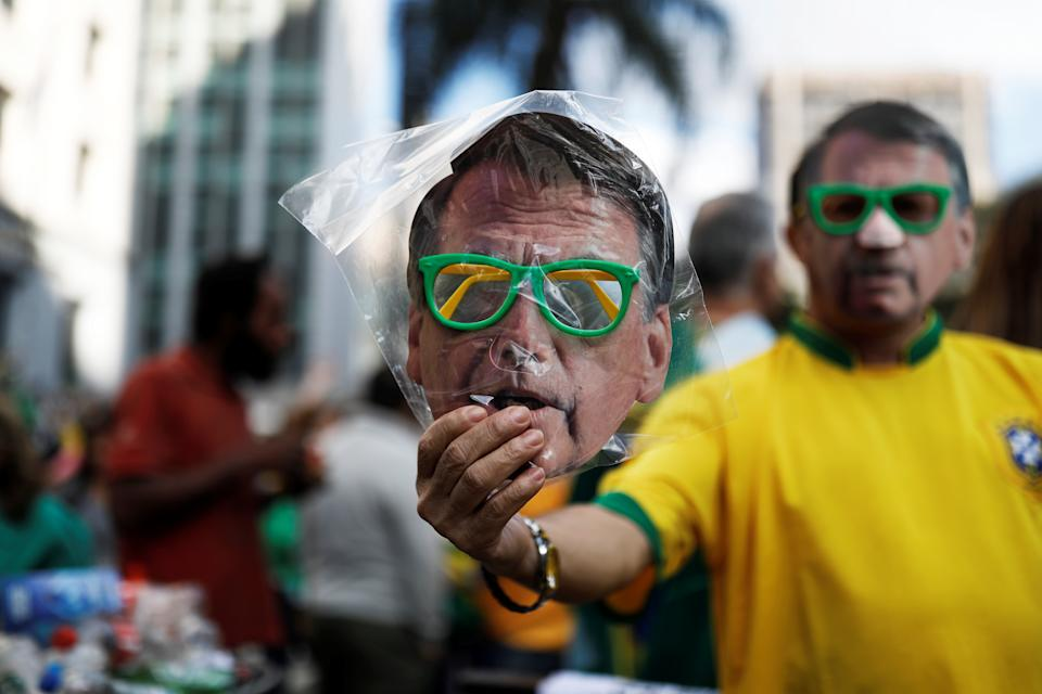 A street vendor sells a mask of Jair Bolsonaro, far-right lawmaker and presidential candidate of the Social Liberal Party (PSL), in a demonstration in Sao Paulo, Brazil, October 21, 2018. REUTERS/Nacho Doce       TPX IMAGES OF THE DAY