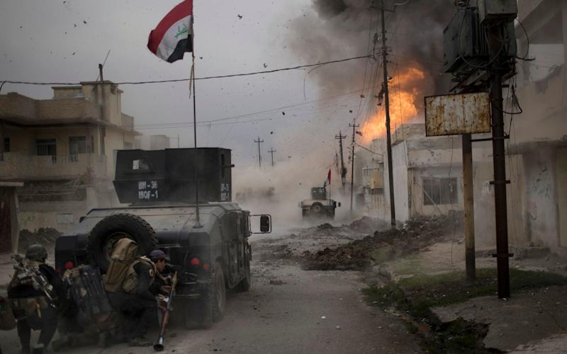 A car bomb exploding next to Iraqi army vehicles during fighting to liberate Mosul - AP