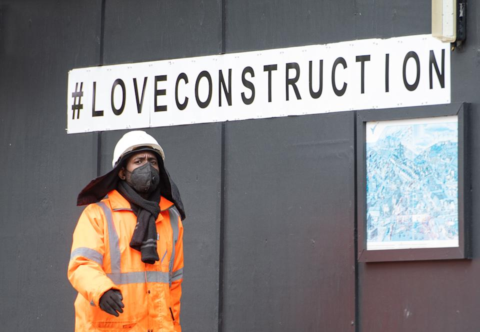 A construction worker wearing a protective face mask at a building site in central London