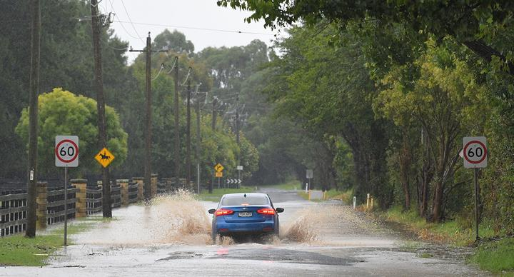 A car is pictured driving through flood waters in Sydney's Richmond on March 20, 2021.
