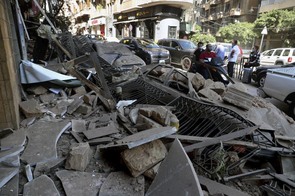 Men on a scooter pass cars and buildings that were damaged after a massive explosion on Tuesday, in Beirut, Lebanon, Wednesday, Aug. 5, 2020. The explosion flattened much of a port and damaged buildings across Beirut, sending a giant mushroom cloud into the sky. In addition to those who died, more than 3,000 other people were injured, with bodies buried in the rubble, officials said. (AP Photo/Bilal Hussein)