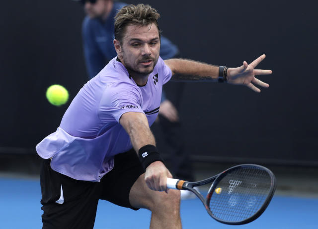 Switzerland's Stan Wawrinka makes a backhand return to Latvia's Ernests Gulbis during their first round match at the Australian Open tennis championships in Melbourne, Australia, Tuesday, Jan. 15, 2019. (AP Photo/Kin Cheung)