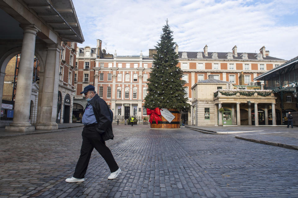 A man wearing a face mask passes the Christmas tree in Covent Garden Piazza, as England continues a four week national lockdown to curb the spread of coronavirus, in London, Tuesday, Nov. 17, 2020. (Dominic Lipinski/PA via AP)