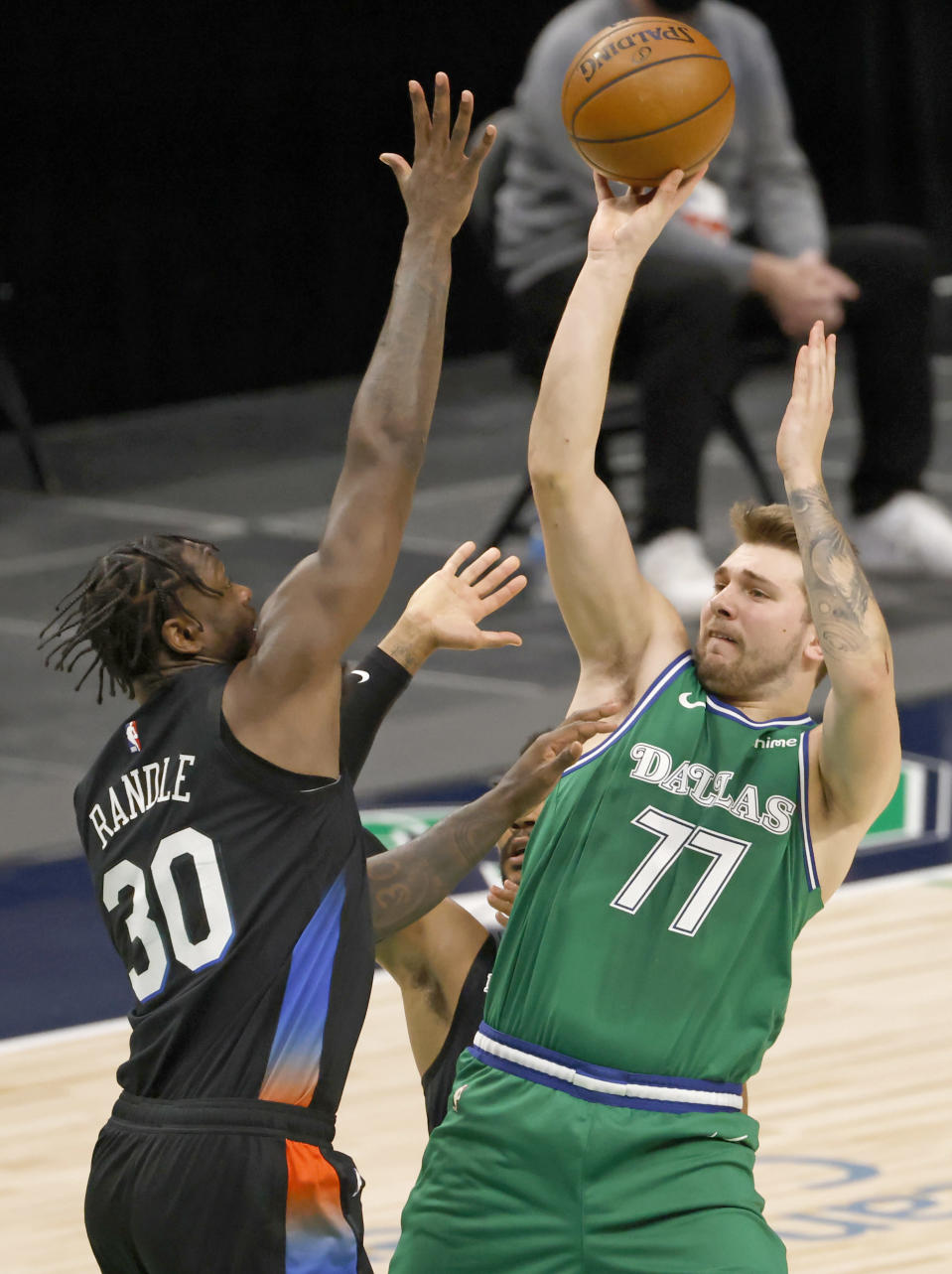 Dallas Mavericks guard Luka Doncic (77) shoots the ball as New York Knicks forward Julius Randle (30) goes up to defend during the first half of an NBA basketball game, Friday, April 16, 2021, in Dallas. (AP Photo/Ron Jenkins)