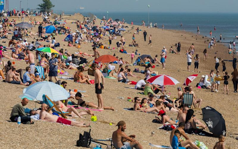 Crowds of people visiting Southend beach during hot and sunny weather in Southend, Essex, Britain, 21 May, 2020. As the UK starts easing its lockdown restrictions, many workers across the country are facing the dilemma of whether returning to their workplaces is safe for them or not. Meanwhile, the UK's economy has suffered a 2-percent fall, its worst decline since the 2008 financial crash, due to the global effects of the ongoing pandemic of the COVID-19 disease caused by the SARS-CoV-2 coronavirus. Coronavirus in Britain, Southend - Shutterstock