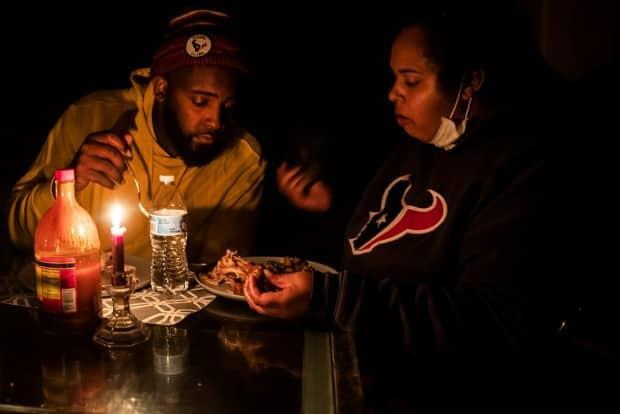 Howard and Nena Mamu have dinner at their home by candlelight after power companies performed rotating outages in Glenwood neighbourhood in Hutto, Texas, on Tuesday. According to Joshua Rhodes and Blake Shaffer, there are lessons Albertans need to learn after this week's massive power outages in the U.S. state.