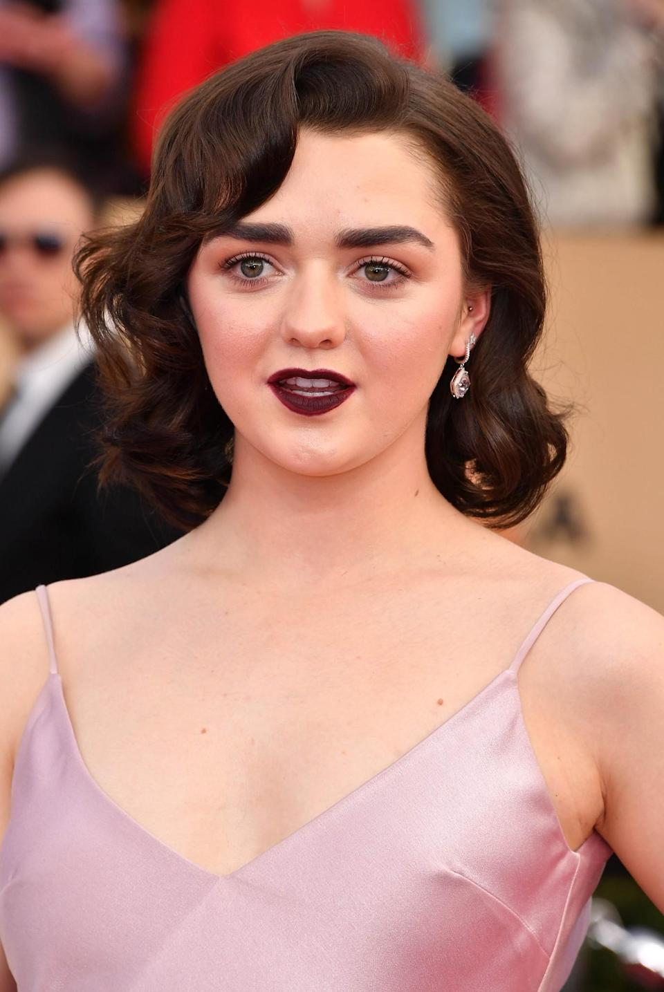 <p>Always one to put a slight edge on her red carpet outfits, Maisie Williams paired her girly pink dress with vampy hair and make-up. She did this effortlessly by modelling an oxblood lip and big retro curls. [Photo: Getty] </p>