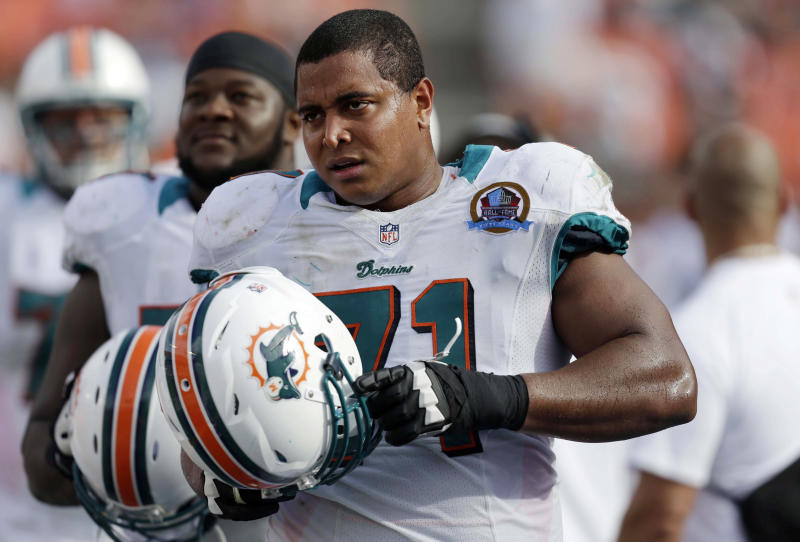 "FILE - In this Dec. 16, 2012 file photo, Miami Dolphins tackle Jonathan Martin (71) watches from the sidelines during the second half of an NFL football game against the Jacksonville Jaguars, in Miami. Martin was subjected to ""a pattern of harassment"" that included racist slurs and vicious sexual taunts about his mother and sister by three teammates, according to a report ordered by the NFL. AP Photo/Wilfredo Lee, File)"