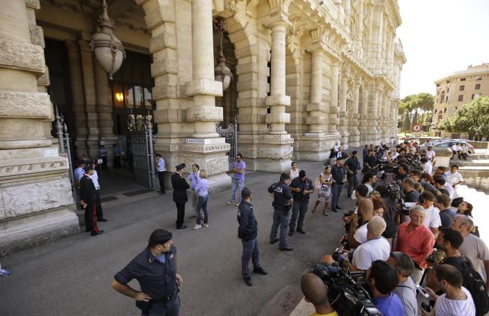 Journalists crowd outside the Court of Cassation building where Berlusconi's case on tax fraud will be decided, in Rome, Thursday, July 31, 2013. Berlusconi's political fate is in the hands of Italy's highest court, which is preparing to hear arguments in the former premier's fraud conviction. Berlusconi has been convicted of tax fraud in a complex TV rights transaction for his Mediaset network, and sentenced to four-years in prison with a five-year ban on public office. This is his final appeal. (AP Photo/Gregorio Borgia)
